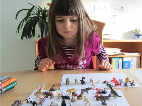 Mädchen spielt mit Plastiktieren