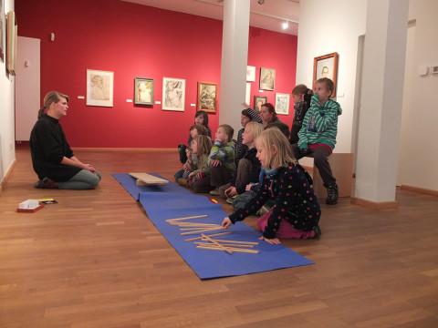 Schüler_innen beim Besuch des Stadtmuseums, während sie gerade das Arbeitsfeld der Museumspädagogin erklärt bekommen.