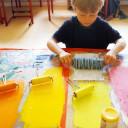 Wackelzahn_Kunstwoche unserer drei QuerWege-Kita's_Kunstwerke der Druckwerkstatt_Rollengestaltung mit der Farbe zur Vorbereitung des Druckes