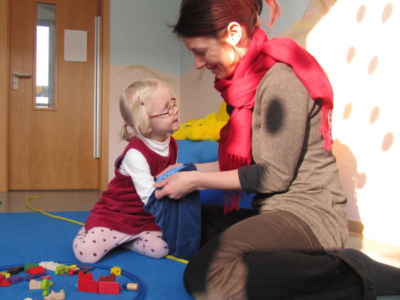Kleines Mädchen spielt mit Pädagogin